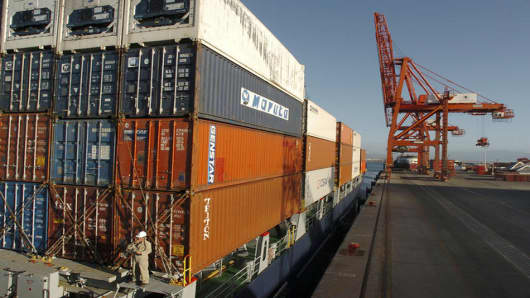 Shipping containers lay stacked on a cargo ship docked at the Ensenada International Terminal port facility on Wednesday, March 8, 2006 in Ensenada, Mexico. In March 2005, the facility acquired two additional cargo cranes, seen in the background, bringing the total to four. Mexico and some of the world's largest retailers and shipping interests are bolstering Pacific ports south of the border, hoping to catch future runoff as an increasing tide of Asian cargo sails toward already clogged ports i