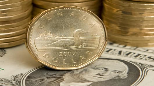 A Canadian dollar, or loonie, sits in front of its American counterpart in Toronto on Thursday, Sept. 20, 2007. The Canadian dollar reached parity with the US dollar this morning for the first time since November 1976. (AP Photo/Adrian Wyld, The Canadian Press)