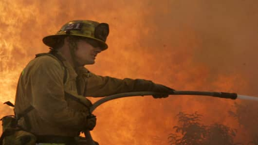 A Los Angeles County firefighter braces against wind and flames as fire leaps across Rambla Pacifico in the Santa Monica Mountains.