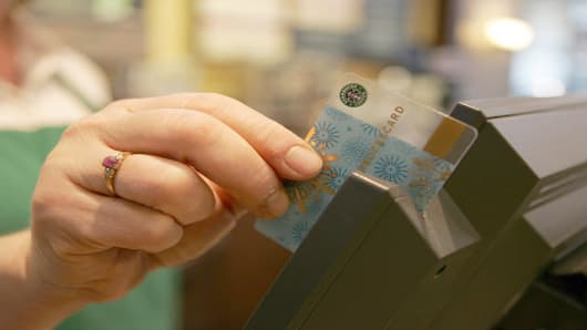 A Starbucks gift card is swiped at the register of a Starbucks store.
