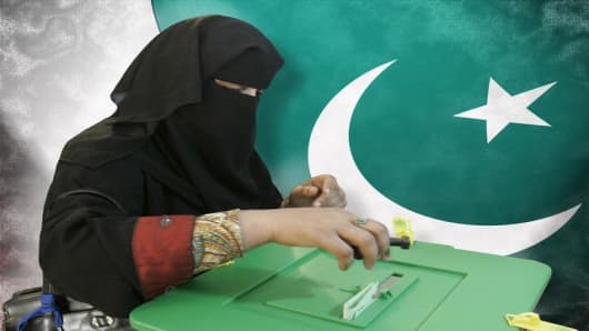 Pakistani woman voter casts her vote in the conservative city of Peshawar, Pakistan on Monday, Feb. 18, 2008. Pakistanis voted Monday for a new parliament in elections shadowed by fears of violence and questions about the political survival of President Pervez Musharraf, America's key ally in the war on terror. (AP Photo/B.K.Bangash)