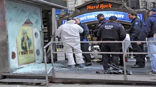 "New York City police officers investigate the scene at a military recruiting station in New York's Times Square on Thursday, March 6, 2008. An explosive device caused minor damage to the landmark recruiting station before dawn Thursday, prompting a huge police response that disrupted transit at the ""crossroads of the world."" (AP Photo/Louis Lanzano)"