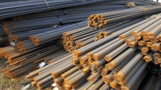 A Chinese worker walks near steel bars at a market in Shenyang, northeastern China's Liaoning province Sunday April 15, 2007. China will cut export tax rebates on steel, an industry group announced last week, amid pressure on Beijing to rein in rapid growth in exports.(AP Photo) ** CHINA OUT **