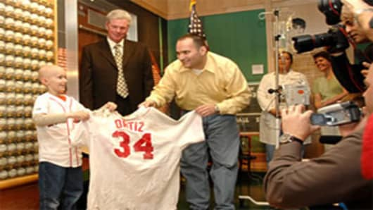 Jimmy Fund Chairman Mike Andrews (center) and Dana-Farber patients Ryan Reardon (left) and Gerry House unveil the jersey in the Jimmy Fund Red Sox Gallery at Dana-Farber.