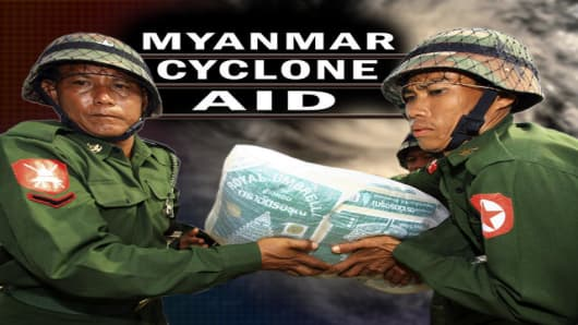 Myanmar soldiers carry sacks of rice, part of aid supplied by the Thai government, at an airport in Yangon, Myanmar Tuesday, May 6, 2008. Myanmar's Irrawaddy delta, where nearly 22,000 people perished, remained largely cut off from the rest of the world Tuesday, four days after a cyclone unleashed winds, floods and high tidal waves on the densely populated region. (AP Photo)