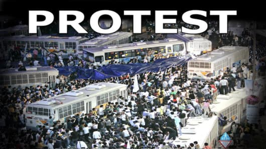 South Korean protesters surround police buses as police block them during a rally against U.S. beef imports in Seoul, South Korea, Monday, June 2, 2008. President Lee Myung-bak showed no signs Sunday of dropping a plan to allow U.S. beef imports after nearly 40,000 people took to the streets in a major anti-government protest marked by clashes between police and demonstrators. (AP Photo/Ahn Young-joon)