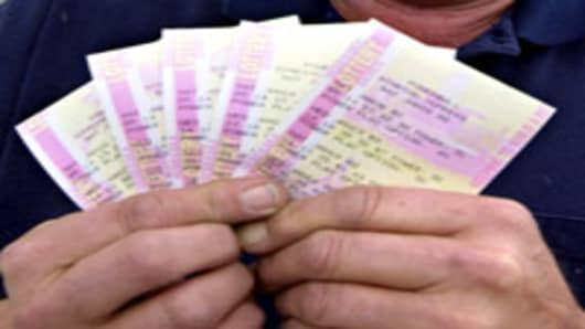 Powerball lottery tickets held in hand.