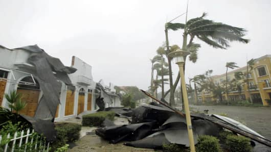 Parts of a roof lie on the sidewalk as trees sway in the winds of Hurricane Wilma Monday, Oct. 24, 2005 in downtown Naples, Fla. Hurricane Wilma crashed ashore early Monday as a strong Category 3 storm, battering southwest Florida with 125 mph winds. (AP Photo/Wilfredo Lee)