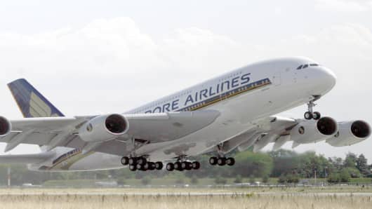 ** FILE ** The first Airbus A380 for Singapore Airlines takes off from the Airbus plant in Hamburg in this July 19, 2007 file photo. Woes at Airbus, including the cost of redesigning the mid-range A350 jet and the delayed A380 superjumbo, caused second-quarter earnings at European Aeronautic Defence & Space Co. NV to slump 85 percent, the company said Thursday, July 26, 2007. (AP Photo/Patrick Lux, file)