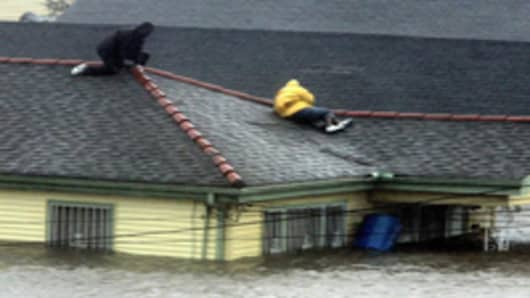 Two people take refuge on their roof top as Hurricane Katrina hits, causing flooding in their New Orleans neighborhood in 2005.