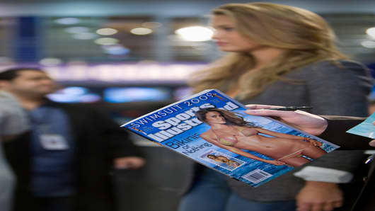 Darren Holds the new Sports Illustrated swimsuit special with cover model Bar Refaeli in the background.