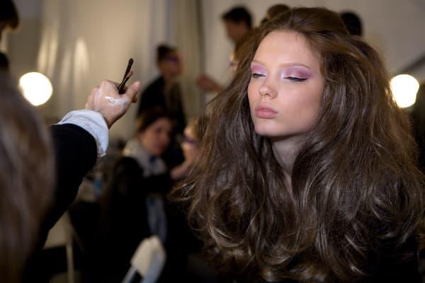 A model gets make up backstage.