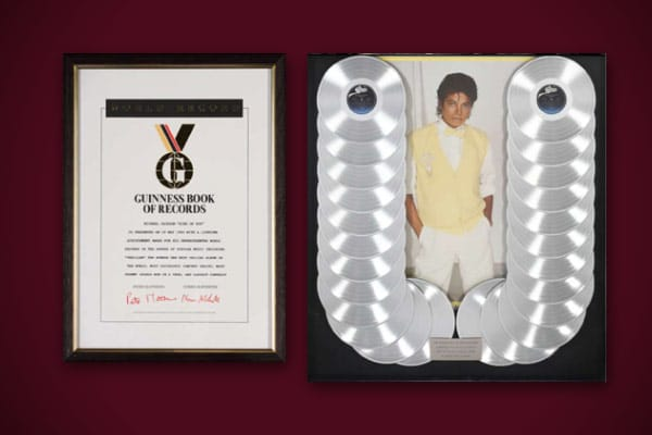 """Commemorative award presented to Michael Jackson from the Guinness Book of World Records for """"...the biggest selling album in the history of music."""" The display features a poster of Jackson from his Thriller album surrounded by 24 platinum Thriller LPs. Estimated Value: $400 - $600"""