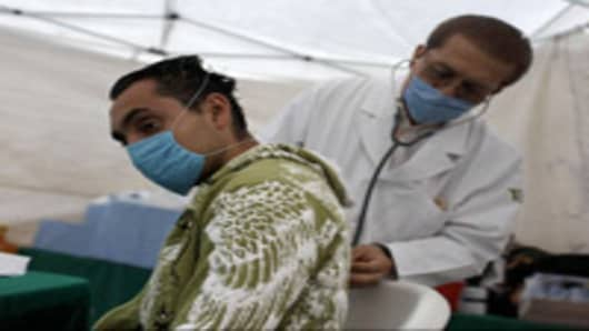 Doctor examines a man at a public health center set up to check for swine flu symptoms
