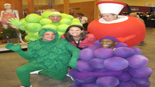 CNBC Producer Lacy O'Toole poses with Fruit of the Loom characters at Berkshire shareholders meeting