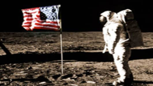 Buzz Aldrin stands on moon surface with US flag during Apollo 11 mission.