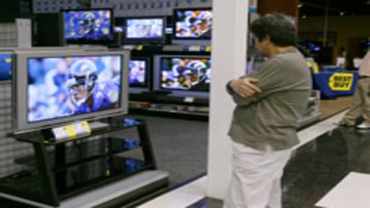 Man watches home theater televisions at the Best Buy