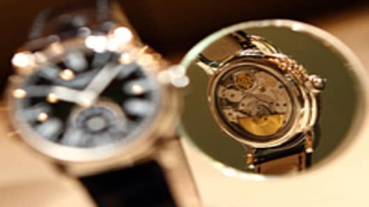 The backside of a Patek Philippe watch is pictured in a mirror.