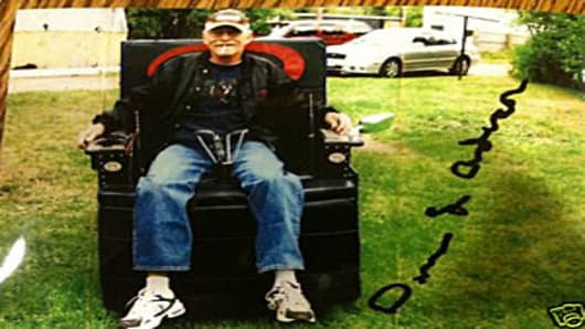 Autographed photo of Dennis L. Anderson in his motorized La-Z-Boy style chair