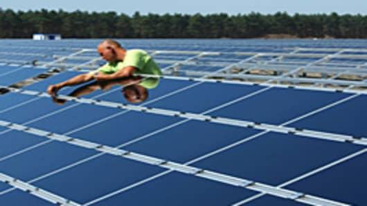 A worker installs solar panels at the Lieberose Solar Park in Lieberose, Germany.