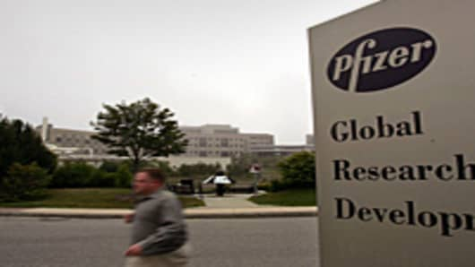 A man walks past a sign for a Pfizer facility in the Fort Trumbull area of New London, Connecticut.
