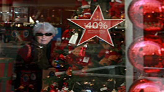 A woman is seen reflected in a Macy's store window as she looks at a Christmas themed window display in San Francisco, California.