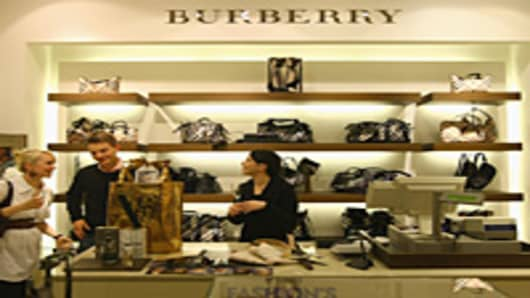 A young couple makes a purchase at a Burberry luxury store.