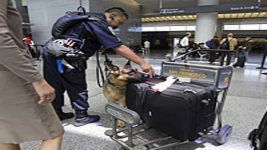 Sgt. Cliff Java of the San Francisco police department and his dog check the luggage in the ticketing area of the International Terminal at the San Francisco International Airport in San Francisco, California.