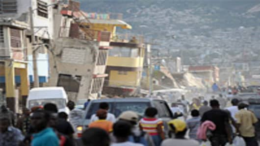 Pedestrians walk along a street destroyed by a massive earthquake that rocked Haiti, in Port-au-Prince.