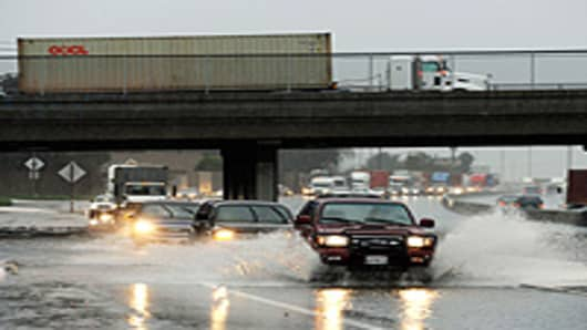 Cars and commercial trucks make their way through the flooded southbound lanes of the 710 Long Beach Freeway, the main artery to Long Beach and Los Angeles ports, on January 20, 2010 in Long Beach, California.