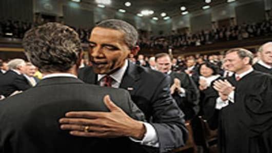 U.S. President Barack Obama greets Treasury Secretary Timothy Geithner as the president enters the House to give his first State of the Union speech