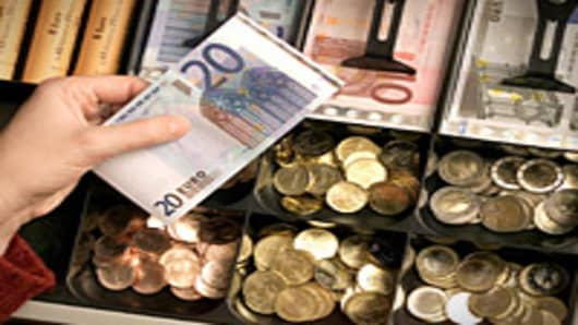 Euro bills and coins in cash register tray