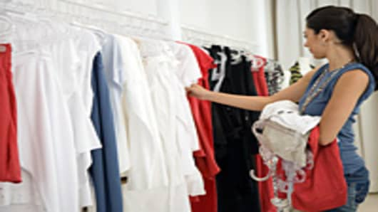 Woman selecting clothes from rail in shop