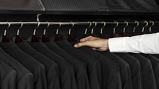 Man selecting a jacket from a clothing rack