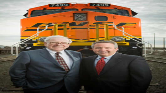 "Warren Buffett and BNSF Chairman Matthew Rose ""pose in front of one of BNSF's new, fuel-efficient locomotives."""