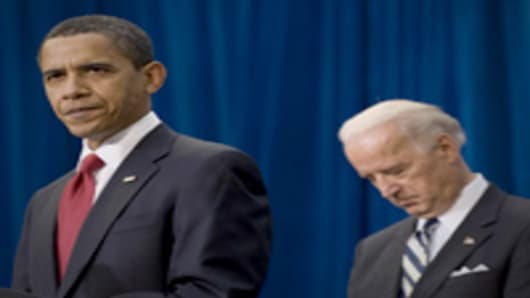 US President Barack Obama speaks with US Vice President Joe Biden before signing the American Recovery and Reinvestment Act at the Denver Museum of Nature and Science in Denver, Colorado, February 17, 2009.