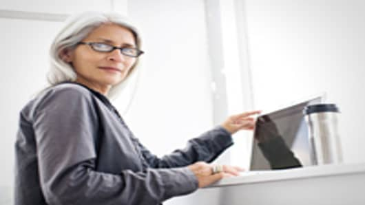 Gray haired woman working on laptop