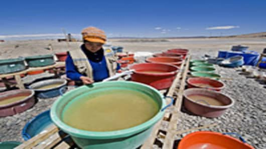 Bolivian chemical engineer Monica Aguirre poses with plastic containers with brine at a pilot lithium plant in Uyini, Bolivia. The Uyuni Salt flats has one of the biggest reserves of lithium in the world, estimated in 100,000 metric tons.