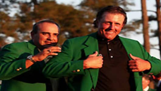 Angel Cabrera of Argentina presents Phil Mickelson with the green jacket during the green jacket presentation after the final round of the 2010 Masters Tournament at Augusta National Golf Club in Augusta, Georgia.