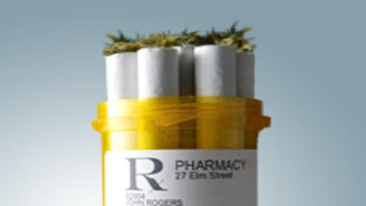 A pharmaceutical pill bottle with marijuana cigarettes coming out of the top.