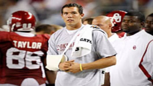 Quarterback Sam Bradford #14 of the Oklahoma Sooners stands on the sidelines after suffering an injury against the Brigham Young Cougars at Cowboys Stadium on September 5, 2009 in Arlington, Texas.