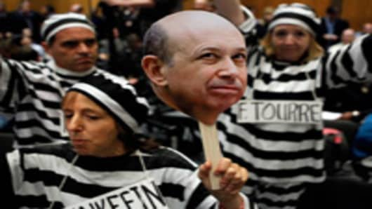 Demonstrators from Code Pink for Peace hold photographs of Lloyd Blankfein, chairman and CEO of The Goldman Sachs Group, and demand he be jailed with other executives before a hearing of the Senate Homeland Security and Governmental Affairs Investigations Subcommittee on Capitol Hill.
