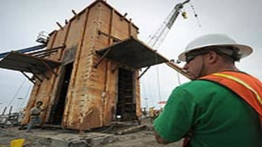 A safety officer watches as the Pollution Control Dome is built by steelworkers at the Martin Terminal worksite in Port Fourchon, as BP rushes to cap the source of the oil slick from the BP Deepwater Horizon platform disaster in Louisiana.