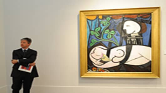 "A man stands beside Pablo Picasso's ""Nude, Green Leaves and Bust"", 1932, on display April 29, 2010 at Christie's in New York."