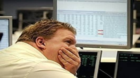 A stock broker sits in front of a board displaying German share index DAX at the stock exchange in Frankfurt/M., western Germany.