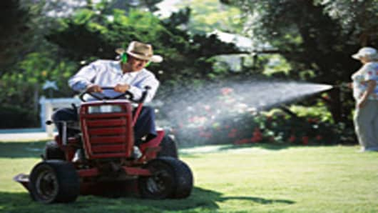 Man mowing and woman watering lawn