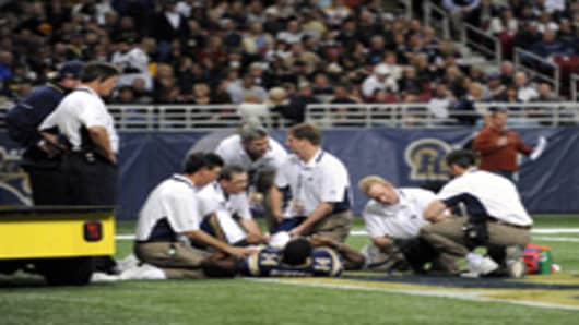 Keenan Burton of the St. Louis Rams is looked at by team physicians after suffering a season-ending knee injury.