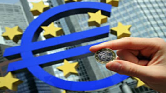 Euro coin in front of the giant symbol of the Euro outside the headquarters of the European Central Bank.