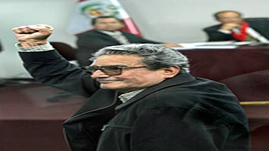 Abimael Guzman, founder and leader of the moaist guerrilla Sendero Luminoso (SL) (Shining Path) salutes with a clenched-fist at the beginning of a trial against him on November 05th, 2004.