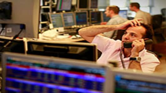 A trader looks worried as he works in a dealing room in Tel Aviv, Israel.